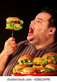 Diet failure of fat man eating fast food . Happy smile overweight person who crazy makes squint for fun eating huge hamburger on fork. Junk meal leads to obesity. Man suffers from gluttony.