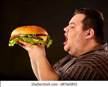 Diet failure of fat man eating fast food hamberger. Breakfast for overweight person who spoiled healthy food by eating huge hamburger. Junk meal leads to obesity. Cooking hamburgers at home.