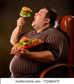 Diet failure of fat man eating fast food hamberger. Happy overweight person with wide-open mouth greedily eating huge hamburger on fork. Hate to diets. Business chairs for fat people concept.