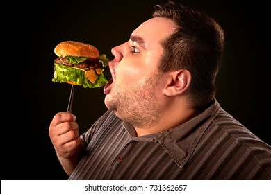 Diet failure of fat man eating fast food. Happy smile overweight person who crazy makes squint for fun eating huge hamburger on fork. Use of semi-finished products for food. Man suffers from gluttony.