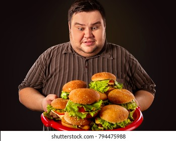 Diet failure of fat man eating fast food. Happy smile overweight person who crazy makes squint for fun eating huge hamburger on fork. Food is main thing in life. Man suffers from gluttony.
