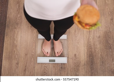 Diet And Fast Food Concept. Overweight Woman Standing On Weighing Scale Holding Burger ( Hamburger ). Unhealthy Junk Food. Dieting, Lifestyle. Weight Loss. Obesity. Top View
