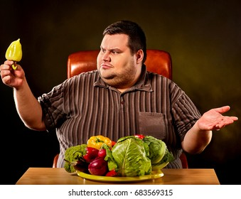Diet fat man eating healthy food with a lot of vegetables for overweight person. Male trying to lose weight and rejoices at advent of summer and vitamins. He hates healthy food idea.