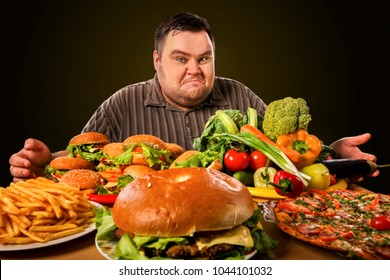 Diet fat man who makes choice between healthy and unhealthy food . Overweight male with hamburgers, french fries. Feast on the occasion of the feast.