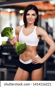 Diet and fitness concept. Self confident athletic girl fitnes instructor with perfect body encourages to healthy diet holding big broccoli as a dumbell on background of gym