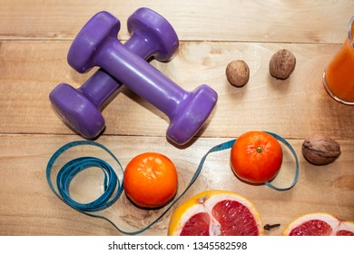 Diet. Fitness and healthy diet concept. Balanced diet with vegetables. Measuring tape on the background of dumbbells. Close-up. View from above.