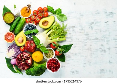 Diet food concept: fresh vegetables and fruits on white wooden background. Free space for your text.