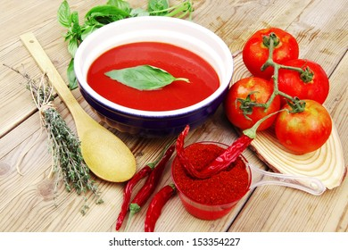 diet food : fresh cold tomato soup with basil thyme and dry pepper in big bowl on wood table