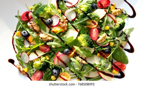 Diet food. Fresh salad with vegetables, fruits and balsamic vinegar on the plate. Top view.