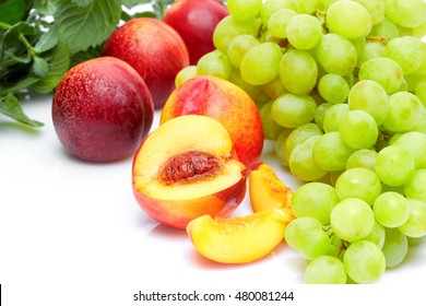 Diet food and healthy lifestyle concept: An aromatic colorful tasty delicious fruits. grapes peaches and mint? Top view. Isolated on white.