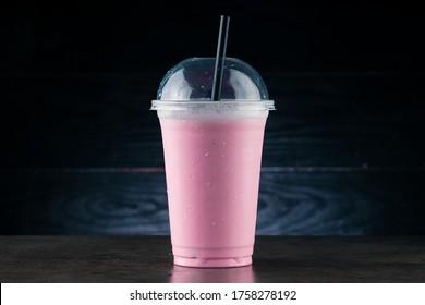 Diet Food and healthy nutrition. Pink Fruit smoothie, cherry milkshake in plastic glass on a dark background. cherry milkshake in takeaway cup