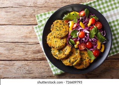 Diet Food: quinoa burgers with spinach and fresh vegetable salad close-up on a plate. Horizontal top view from above