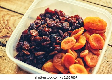 Diet food. Raisins and dried apricots on a wooden table.