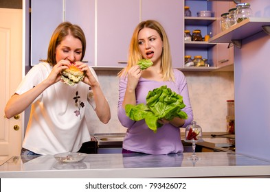 Diet funny concept, one girl eating healthy food green salad and looking at her friend eating tasty burger