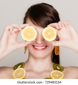 Diet. Girl with necklace of fresh citrus fruits covering eyes with lemons doing fun on gray. Woman recommending healthy food.
