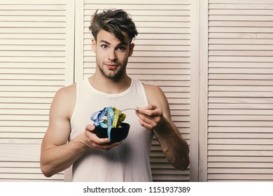 Diet and health concept. Athlete with messy hair and unshaved face. Guy in sleeveless shirt eating measuring tape. Man with surprised face expression on background of beige jalousie.