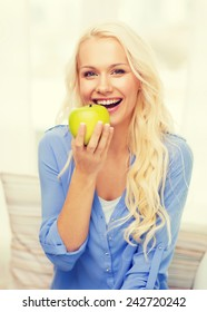 diet, health and home concept - smiling yoing woman with green apple at home