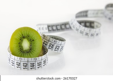 Diet and health - A kiwi fruit, halved and surrounded by a measuring tape on a white background