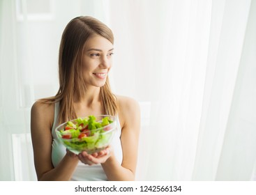 Diet and health. Young woman eating healthy salad after workout.