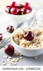 Diet and healthy breakfast i: oatmeal with cherries in a white plate on a gray tablecloth, in the background dish with cherries and a can of oatmeal