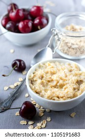 Diet and healthy Breakfast: oatmeal with cherries in a white plate on a gray tablecloth, in the background dish with cherries and a can of oatmeal