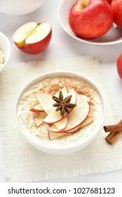 Diet healthy breakfast. Oatmeal porridge with red apple slices and cinnamon.