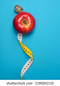 Diet or healthy eating concept with a measuring tape and organic apple