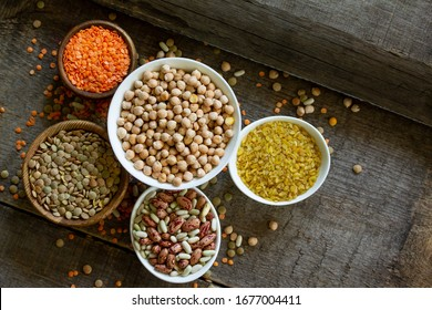Diet and healthy eating concept, vegan protein source. Raw of legumes (chickpeas, red lentils, canadian lentils, beans, bulgur). Top view on a flat lay. Copy space.