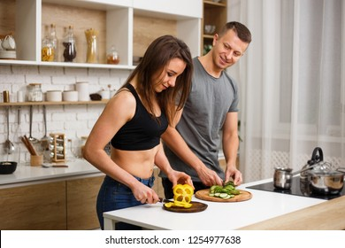 diet, healthy eating, fitness lifestyle, proper nutrition. health conscious couple cooking low calorie dinner in home kitchen