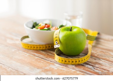 diet, healthy eating, food and weigh loss concept - close up of green apple and measuring tape with salad on wooden table