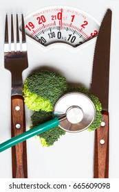 Diet healthy eating weight control and health care concept. Closeup green broccoli with stethoscope knife fork on white scales
