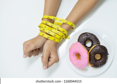 Diet or healthy food concept : Top view of  two hands of young woman been tied by measuring tape for prevent eating unhealthy food such as donut or sweet during diet program.