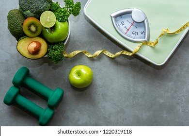 Diet and Healthy life loss weight slim Concept. Organic Green apple and Weight scale measure tap with nutrition vegan vegetable and sport equipment gym for body women diet fit.  Top view copy space.