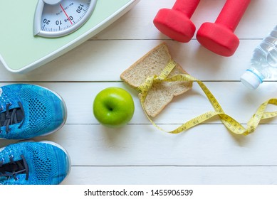 Diet and Healthy life loss weight Concept. Green apple and Weight scale measure tap with fresh vegetable and sport equipment for women diet slimming. Top view and copy space