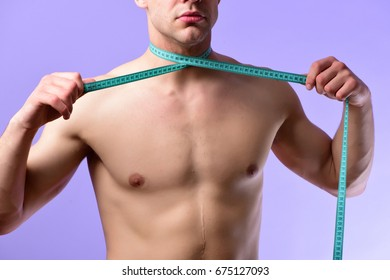 Diet and healthy lifestyle concept. Sports regime idea. Man with naked torso ties measuring tape around his neck. Young sportsman with cyan flexible ruler on light purple background.