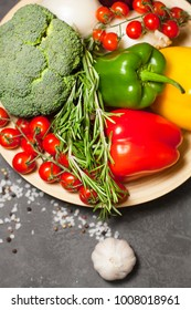 Diet, Healty Food Cooking, Vegetarian Concept. A plate of fresh raw vegetables: cherry tomatoes, broccoli, paprika peppers, rosemary, garlic and spices on a dark table, top view