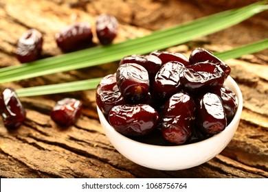 Diet heath concept- organic Arabian raw date fruits in white bowl.