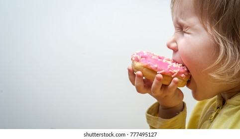 Diet for kids. Happy child eating donuts. Tasty food for kids. Kid is looking on doughnut. junk food addiction.