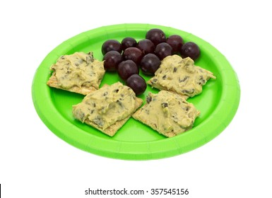 A diet meal of several spinach hommus on whole grain crackers with grapes upon a green paper plate isolated on a white background.