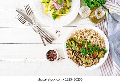 Diet menu. Healthy vegetarian meal - mushrooms shiitake, zucchini  and oatmeal porridge on bowl. Vegan food. Flat lay. Top view