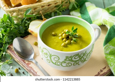 Diet menu. Puree soup with green pea in a bowl on a kitchen wooden table. The concept of healthy eating.