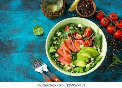 Diet menu, Vegan food. Healthy salad with quinoa, arugula, Tomatoes, Salmon and Avocado on blue concrete or stone table. Top view flat lay background. Copy space.