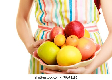 Diet and nutrition. Closeup housewife or seller in striped kitchen apron offering healthy fruits isolated