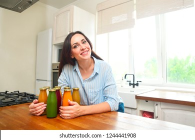 Diet nutrition with detox juice. Healthy woman posing with fresh juice bottles of  detox smoothie. Happy beautiful fit girl In the kitchen