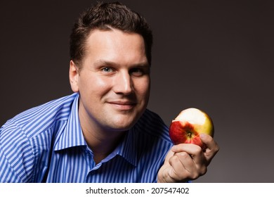 Diet and nutrition. Happy young man eating apple seasonal fruit on dark gray. Guy recommending healthy nutrition.