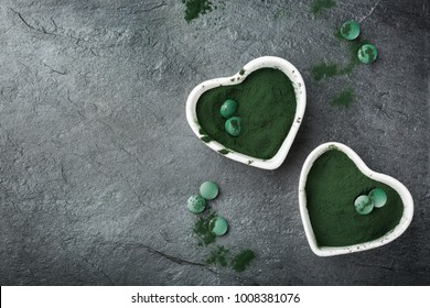 Diet and nutrition, superfood vegan organic healthy lifestyle concept. Ground spirulina algae powder and tablets or pills on a grunge dark table. Copy space background, top view flat lay