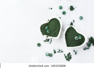 Diet and nutrition, superfood vegan organic healthy lifestyle concept. Ground spirulina algae powder and tablets or pills on a table. Copy space top view background