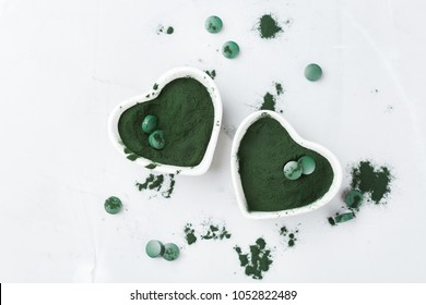 Diet and nutrition, superfood vegan organic healthy lifestyle concept. Ground spirulina algae powder and tablets or pills on a table. Top view background