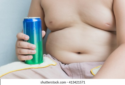 Diet. Obese fat boy holding soft drink can on gray background