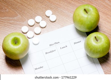 diet Plan. diet plan  and apple lying on a wooden surface